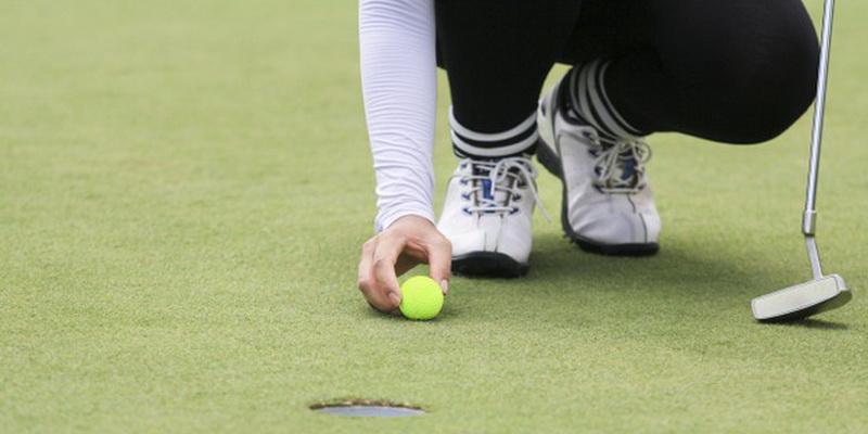 woman golf player putting green